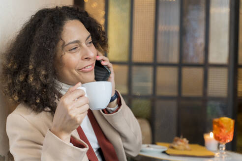 Smiling woman on the phone in a cafe - FMOF00928