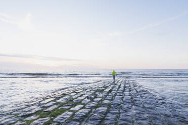 Full length rear view of retired senior man with backpack walking on shore at beach during sunset, North Sea Coast, Flanders, Belgium - GWF06550