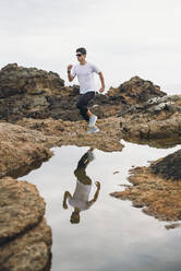 Full length of male trail runner running on rocks with his reflection over water at coast, Ferrol, Galicia, Spain - RAEF02371