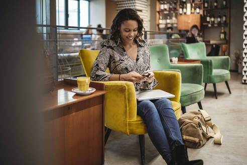 Young woman sitting in armchair using laptop and smartphone - JPIF00453