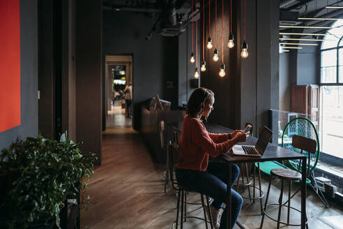Young woman using laptop and smartphone in a cafe - JPIF00483