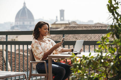 Young woman using laptop and smartphone on a balcony in Florence, Italy - JPIF00495