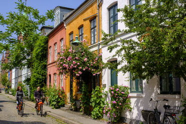 Denmark, Copenhagen, Man and woman riding bicycles along street of historical Nyboder district - LBF02949