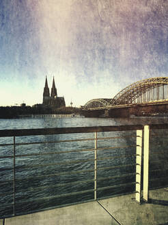Germany, North Rhine-Westphalia, Cologne, Railing of coastal boulevard with Hohenzollern Bridge and Cologne Cathedral in background - GWF06568