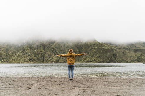 Full length of female tourist with arms outstretched standing at lakeshore in Sao Miguel Island, Azores, Portugal - AFVF05711