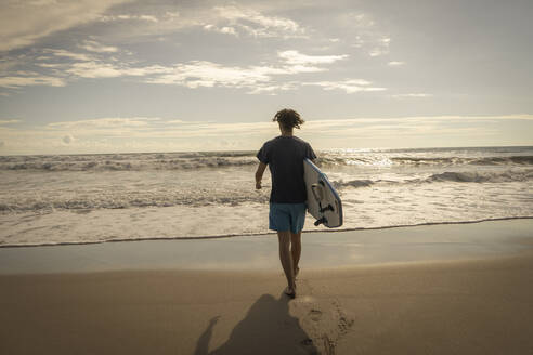Costa Rica, Puntarenas Province, Puntarenas, Rear view of male surfer walking toward ocean with surfboard in hand - TEBF00037