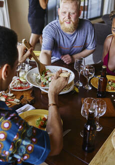 High angle view of multi-ethnic friends eating lunch while sitting at dining table - VEGF01738