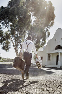 Man in old-fashioned clothes with suitcases in the countryside - RORF02023