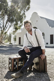 Man in old-fashioned clothes sitting on suitcase in the countryside - RORF02026