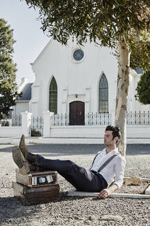 Man in old-fashioned clothes with suitcases leaning against tree trunk in the countryside - RORF02029