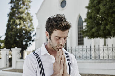 Portrait of man in old-fashioned clothes in the countryside praying at a church - RORF02038