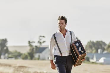 Man in old-fashioned clothes with suitcase in the countryside - RORF02047