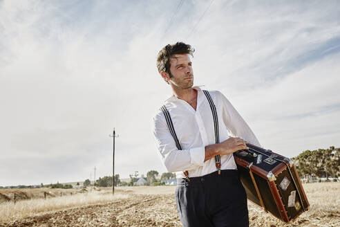 Man in old-fashioned clothes with suitcase in the countryside - RORF02050