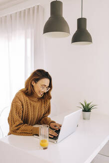 Young woman using laptop on table at home - DCRF00149