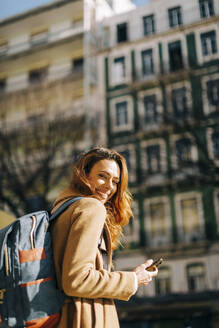 Portrait of happy young woman with backpack in the city, Lisbon, Portugal - DCRF00179
