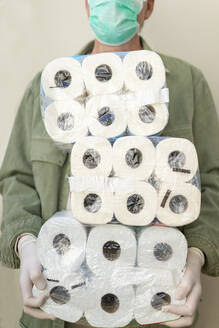 Man with face mask and protective gloves, holding packets of toilet paper - AFVF05769