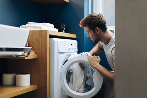 Young man doing the laundry at home - SODF00707