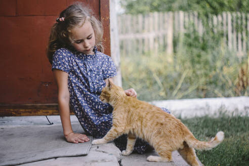 Girl sitting on steps outdoors stroking tabby cat - OGF00261