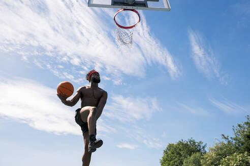 Man playing basketball, dunking - JPIF00498
