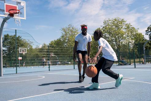 Father and son playing basketball on basketball court - JPIF00510