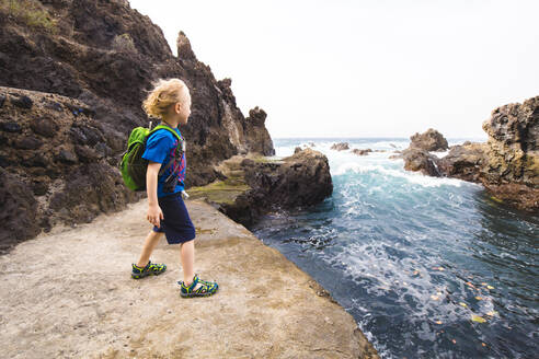 Full length of boy standing on rock formation while exploring sea at Costa Adeje, Canary Islands, Spain - IHF00285
