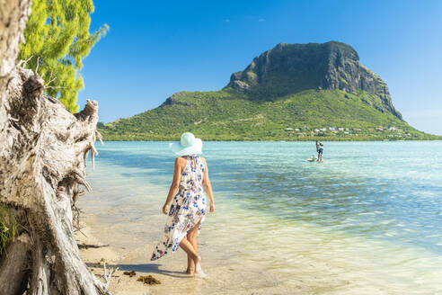 Woman on tropical beach looking at paddleboard in the lagoon, La Gaulette, Le Morne Brabant, Black River, Mauritius, Indian Ocean, Africa - RHPLF14202