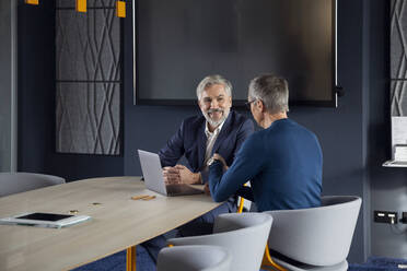 Two smiling businessmen working together on a project in office - RBF07143