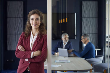 Portrait of confident businesswoman in office with colleagues in background - RBF07152