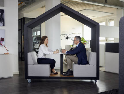 Businessman and businesswoman sitting in a wheeled cubicle in office - RBF07170