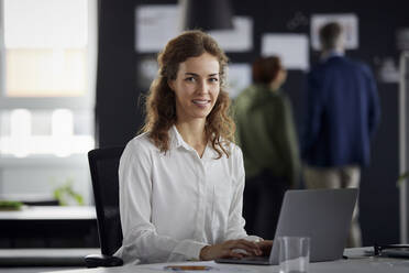 Portrait of smiling businesswoman using laptop at desk in office with colleagues in background - RBF07173