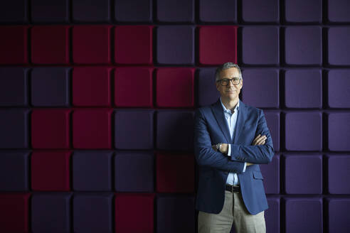 Portrait of confident businessman at a noise reduction wall in office - RBF07206