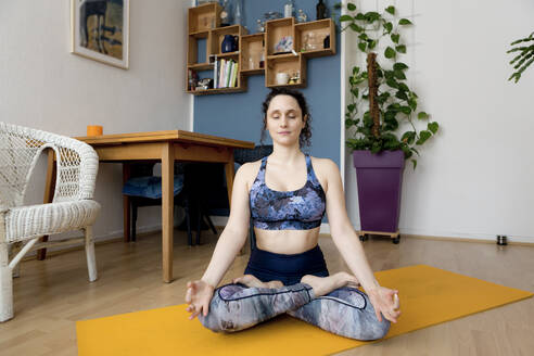 Young woman with closed eyes in yoga pose at home - FLLF00425