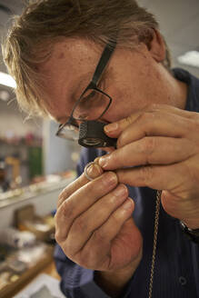 Senior man checking the diamond on a ring with a magnifying glass - VEGF01798