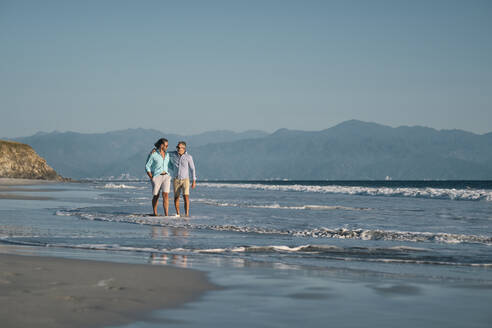 Mature gay men holding hands while walking on shore at beach against clear blue sky, Riviera Nayarit, Mexico - ABAF02295