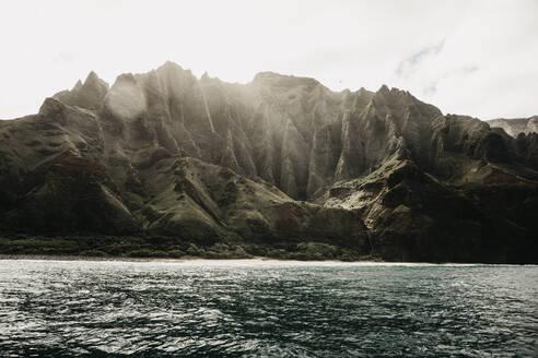 Beautiful mountain range and sea against sky at Nā Pali Coast State Wilderness Park, Kauai, Hawaii, USA - LHPF01177