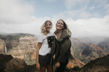 Portrait of happy friends standing against majestic mountains at Waimea Canyon State Park, Kauai, Hawaii, USA - LHPF01186