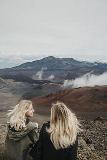 Young friends sitting at Haleakala Crater, Maui, Hawaii, USA - LHPF01192