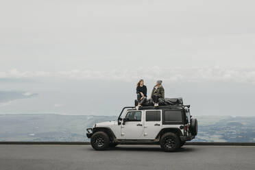 Friends talking while sitting on top of SUV at Maui, Hawaii, USA - LHPF01195