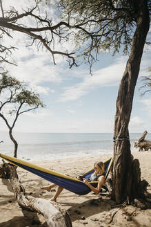 Young woman reading book while resting in hammock at beach, Maui, Hawaii, USA - LHPF01204