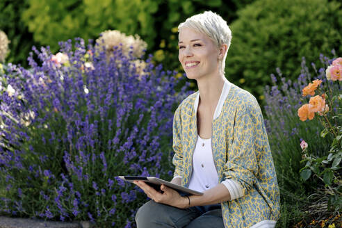 Portrait of happy woman with digital tablet relaxing in a park - FLLF00431