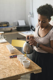 Woman working in a coffee roastery pouring hot water into coffee cups - JPIF00526
