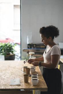Woman working in a coffee roastery preparing coffee - JPIF00532