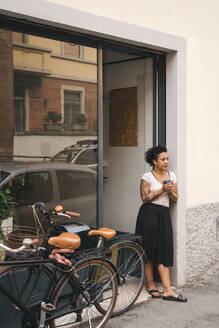 Woman having a coffee break in front of her store - JPIF00553