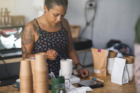 Woman working in a coffee roastery preparing coffee - JPIF00556
