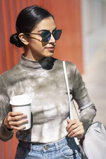Fashionable young woman holding coffee cup while looking away on sunny day - JSMF01477