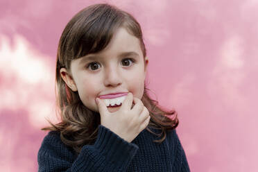 Portrait of little girl with false candy teeth in front of  pink background - GEMF03491