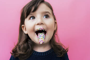 Portrait of happy little girl with sugar granules on lips and tongue in front of  pink background - GEMF03494