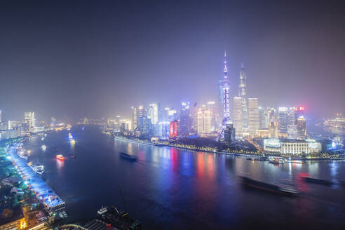 The illuminated skyline of Pudong district in Shanghai with the Huangpu River in the foreground, Shanghai, China, Asia - RHPLF14451