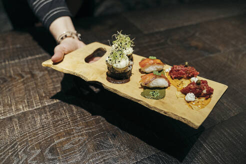 Hand serving Spnaish gourmet food on a board - MTBF00366