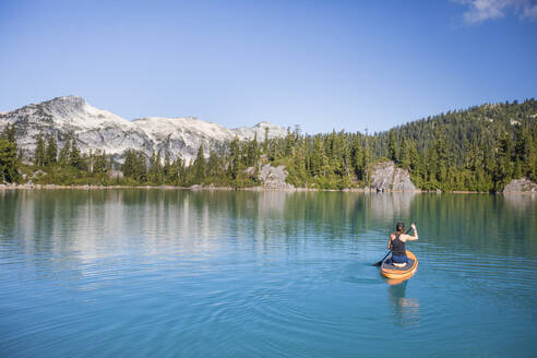 Attractive woman paddles Stand up paddle board on blue lake. - CAVF77438